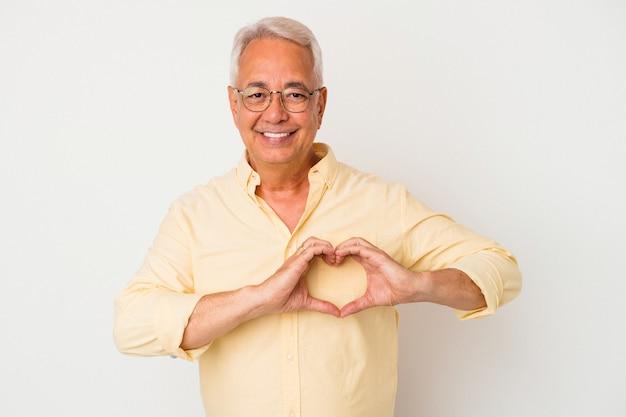 Homme américain senior isolé sur fond blanc souriant et montrant une forme de coeur avec les mains.