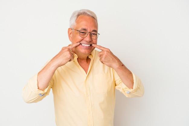 Homme américain senior isolé sur fond blanc sourit, pointant du doigt la bouche.