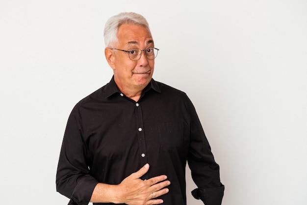 Un homme américain senior isolé sur fond blanc touche le ventre, sourit doucement, mange et satisfait le concept.