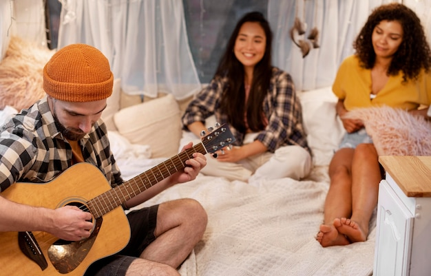 Homme et amis jouant de la guitare