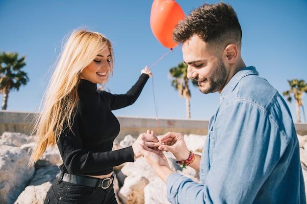 Homme amoureux mettant la bague sur la main des filles