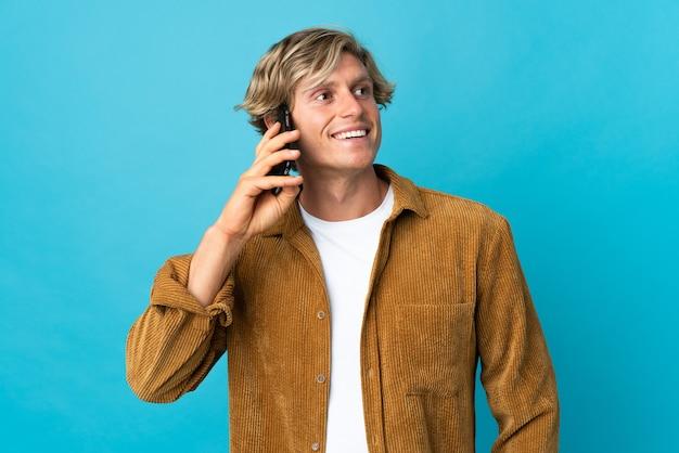 Homme anglais sur bleu isolé en gardant une conversation avec le téléphone mobile avec quelqu'un