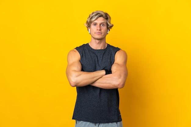 Homme anglais sur mur jaune isolé avec les bras croisés