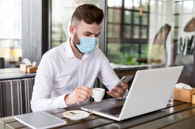 Homme à angle élevé avec masque travaillant à la terrasse