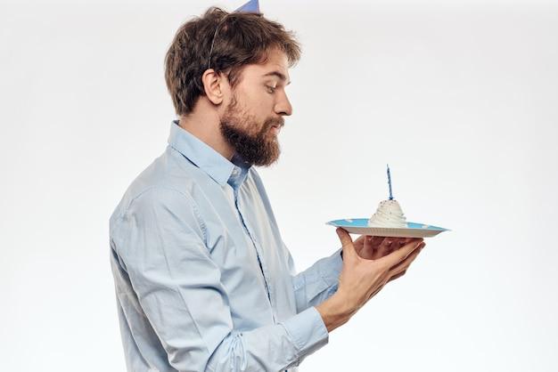 Homme d'anniversaire avec un petit gâteau et une bougie dans un chapeau de fête