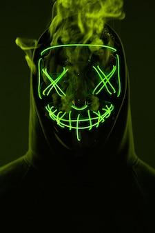 Homme anonyme cachant son visage derrière un masque au néon dans une fumée colorée