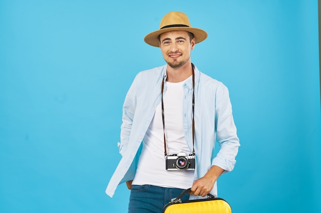 Homme avec appareil photo et chapeau sur fond bleu vue recadrée