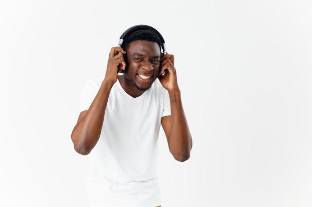 Homme d'apparence africaine dans les écouteurs dans la musique de tshirt blanc