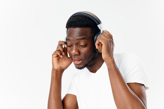Homme d'apparence africaine dans le fond clair d'amant de musique d'écouteurs
