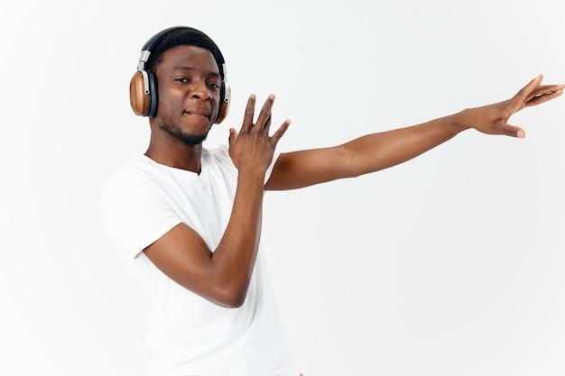 Homme d'apparence africaine dans le fond clair de danse d'amateur de musique d'écouteurs