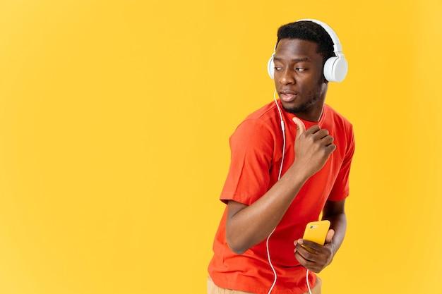 Homme d'apparence africaine avec des écouteurs écoutant de la musique danse sur fond jaune. photo de haute qualité