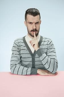 Homme appelant au silence ou révélant un secret. modèle drôle chuchotant à propos de quelque chose. expressions faciales expressives