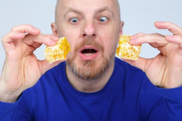 L'homme avec un appétit regarde deux morceaux de miel en nid d'abeille dans ses mains
