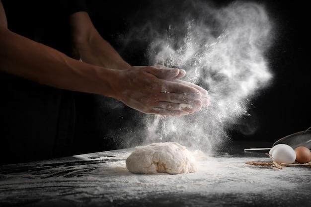 Homme applaudissant et saupoudrer de farine sur la pâte sur fond noir