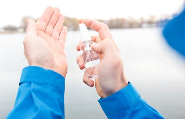 L'homme applique un antiseptique sur sa main en marchant dans le parc