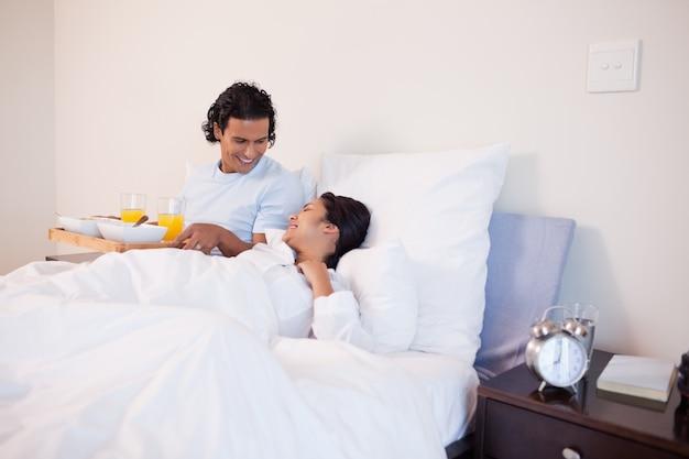 L'homme a apporté le petit déjeuner au lit pour sa petite amie