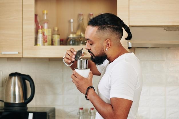 Homme appréciant une délicieuse odeur de café frais qu'il prépare le matin