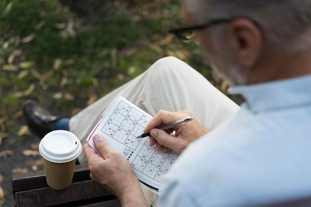 Homme appréciant un jeu de sudoku sur papier par lui-même