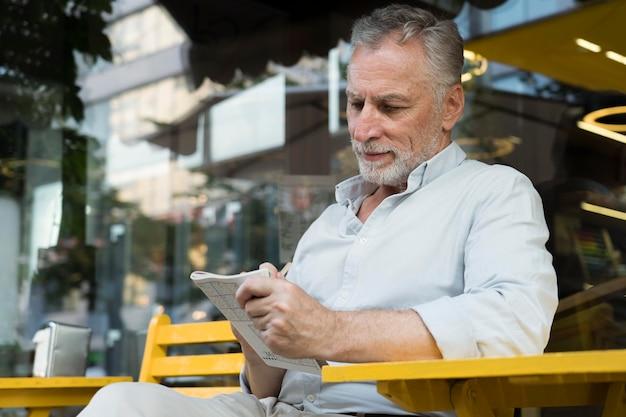 Homme appréciant un jeu de sudoku sur papier