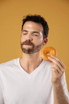 Homme appréciant de manger un beignet
