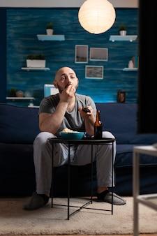 Homme appréciant le temps de se détendre en regardant une série télévisée à la maison