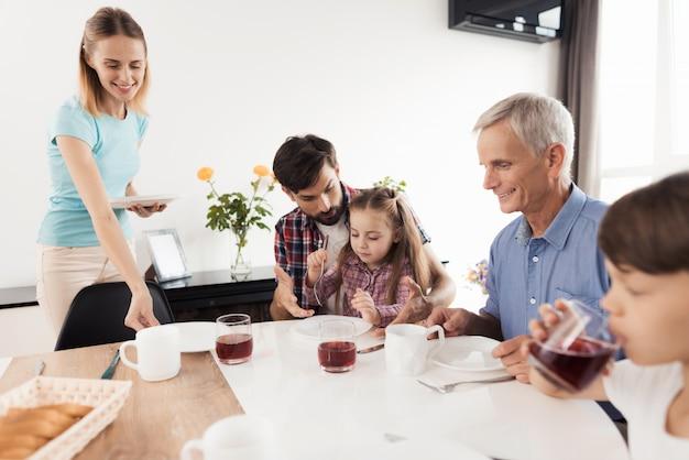 Un homme apprend à une fille à utiliser une fourchette garçon boit le jus d'un verre