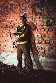 Homme appuyé sur un mur de briques dans une maison inachevée abandonnée