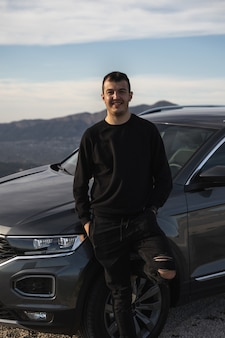 Homme appuyé sur le volant d'une nouvelle voiture gris foncé. vêtu de vêtements sombres et modernes, caucasien, cheveux courts et souriant. journée claire avec quelques nuages et montagnes en arrière-plan.
