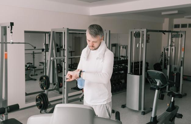 Un homme après une séance d'entraînement intense regarde une montre intelligente. charge cardio