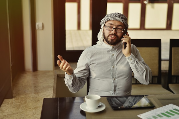L'homme arabe boit du café dans un café.