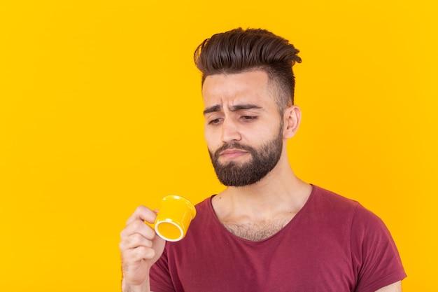 L'homme arabe boit du café dans une petite tasse sur un mur jaune et il n'aime pas ça
