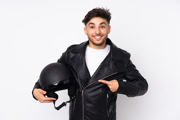 Homme arabe avec un casque de moto isolé sur mur blanc avec une expression faciale surprise