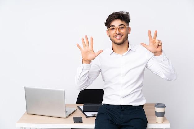 Homme arabe dans un bureau isolé sur fond blanc comptant huit avec les doigts