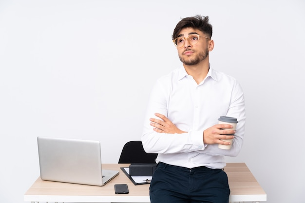 Homme arabe dans un bureau isolé sur fond blanc faisant des doutes tout en soulevant les épaules