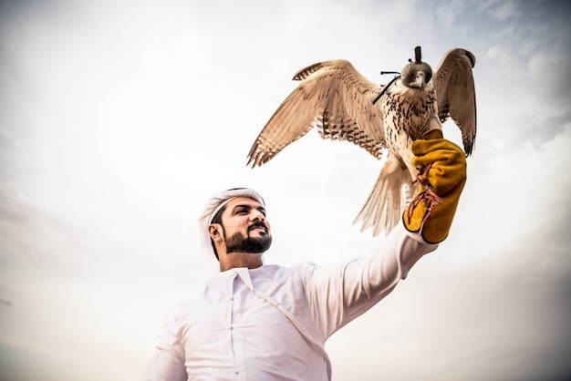 Homme arabe dans le désert avec son faucon