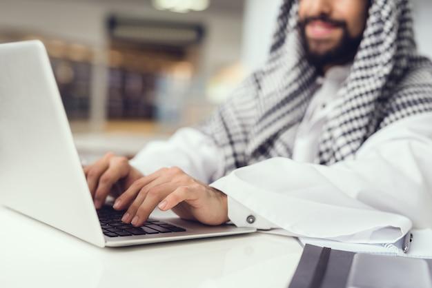 Homme arabe en écharpe à l'aide d'un ordinateur portable au café