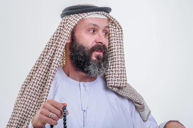 Homme arabe émotionnel posant sur fond blanc.