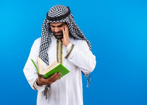 Homme arabe mécontent de l'usure traditionnelle à la recherche de livre avec des émotions négatives debout sur un mur bleu