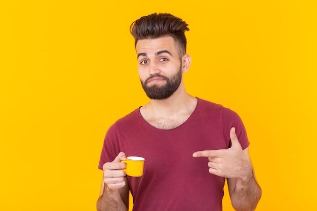 L'homme arabe point sur une tasse de café sur le mur jaune - les gens avec une tasse de café style de vie facile