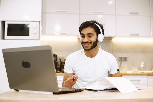Homme arabe regardant un webinaire en ligne, assis dans une cuisine avec ordinateur, profitant d'un apprentissage à distance.
