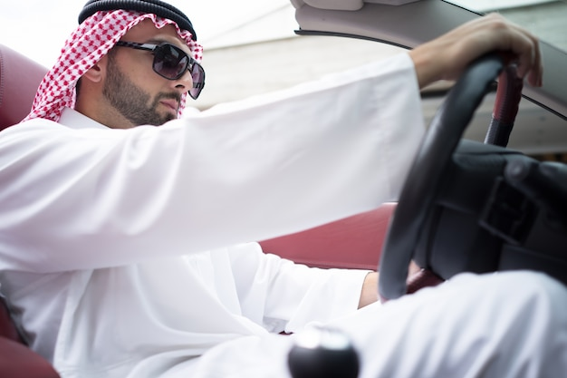 Homme arabe séduisant dans la voiture sur la rue