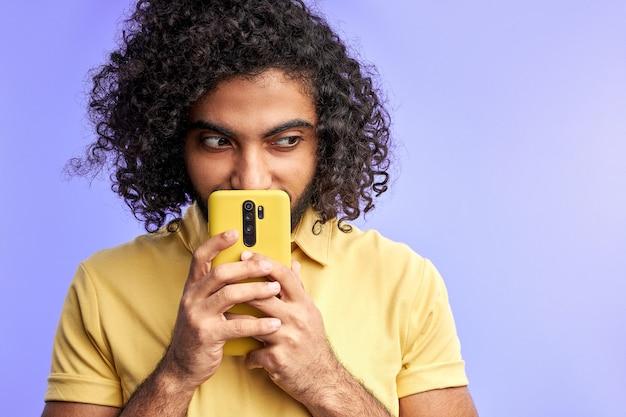 Homme arabe sournois à l'aide de smartphone, pensant quoi écrire dans le message, regardant de côté, isolé sur mur violet