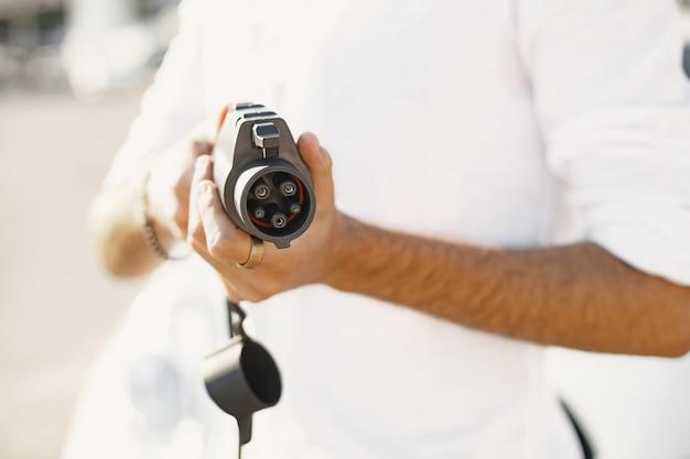 Homme arabe tenant une prise de voiture électrique. souriant à la caméra, debout dans la ville près de la voiture électrique.