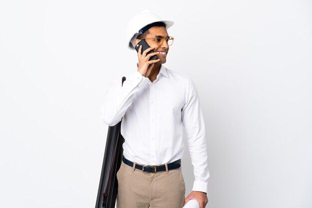 Homme d'architecte afro-américain avec casque et tenant des plans sur blanc isolé
