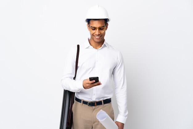 Homme d'architecte afro-américain avec casque et tenant des plans sur fond blanc isolé _ envoi d'un message avec le mobile