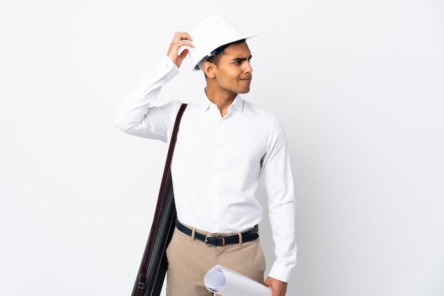 Homme architecte afro-américain avec casque et tenant des plans sur un mur blanc isolé ayant des doutes tout en se grattant la tête