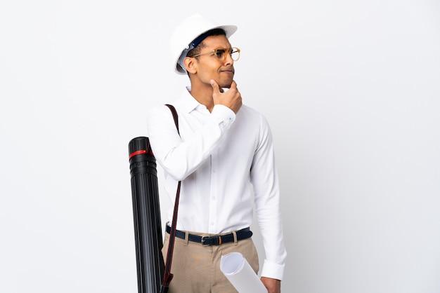 Homme architecte afro-américain avec casque et tenant des plans sur un mur blanc isolé _ ayant des doutes