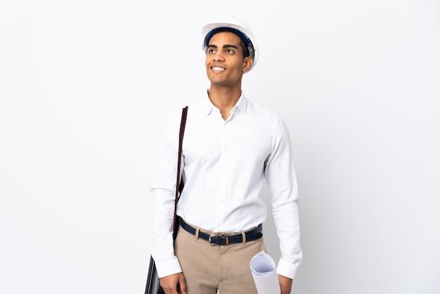 Homme architecte afro-américain avec casque et tenant des plans sur un mur blanc isolé _ penser une idée tout en regardant
