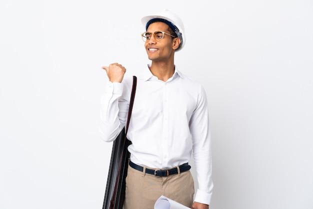 Homme architecte afro-américain avec casque et tenant des plans sur un mur blanc isolé _ pointant vers le côté pour présenter un produit