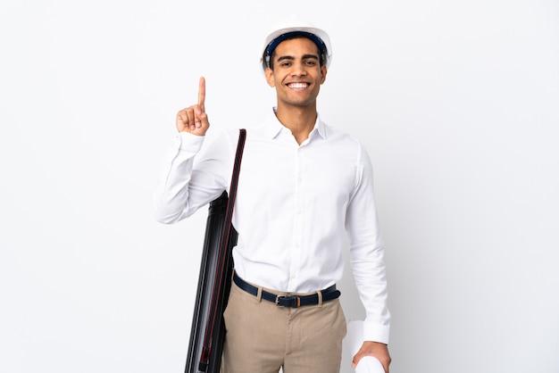 Homme architecte afro-américain avec casque et tenant des plans sur un mur blanc isolé _ pointant vers le haut une excellente idée